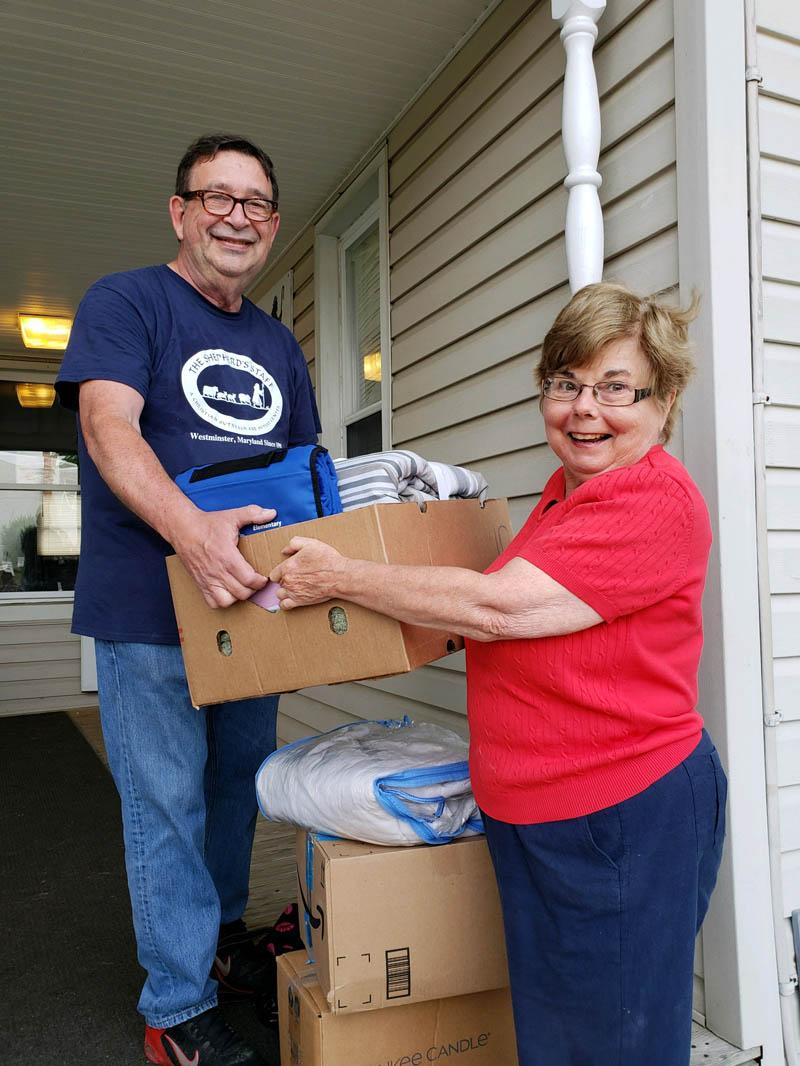 Volunteers take donations for yard sale